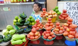 woman amid her carefully stacked vegetables and fruit - Merida, Mexico