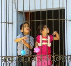children watch a procession from their window - Antigua,Guatemala