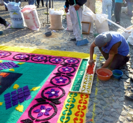 making a sawdust carpet with a stencil for Lent procession - Antigua
