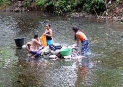 Women washing clothes, in the river below Agua Caliente - Rio Dulce ,Guatemala