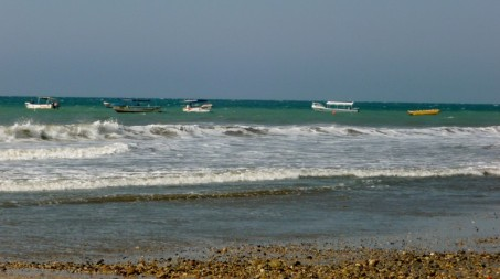 boats bobbing on beach near port in Manta