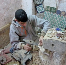 Breaking tile to use for mosaics. Ceramics factory in Fez, Morocco.