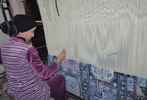 weaving a traditional silk rug, Fez, Morocco.